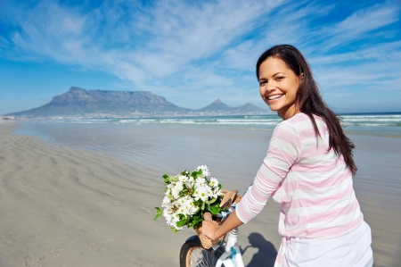 Woman with bicycle on beach in Cape Town, South Africa and Table Mountain photo