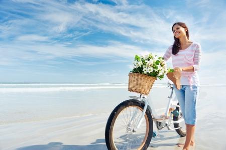 Mujer con la bicicleta y las flores en la canasta sonrisa despreocupada y feliz