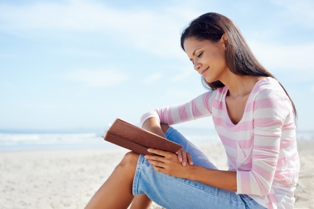 pleasure of reading: woman reading and relaxing on beach with book