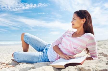 woman reading and relaxing on beach with book photo