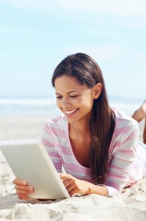 fiestas electronicas: Mujer despreocupada utiliza la tecnolog?de tableta touchpad en la playa con las vacaciones de internet Foto de archivo