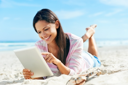 fiestas electronicas: Mujer despreocupada utiliza la tecnología de tableta touchpad en la playa con las vacaciones de internet