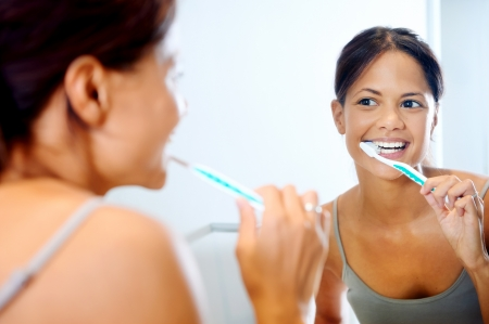 Portrait of attractive woman brushing teeth in bathroom and looking in the mirror at reflection. healthy teeth. Stock Photo - 19385147