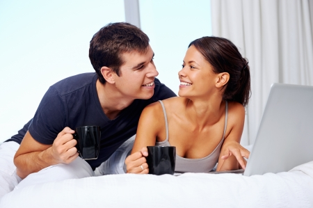 young couple enjoy coffee and relax at home with laptop and love Stock Photo - 19385154