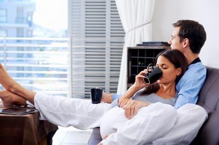 Echtpaar ontspannen thuis met een kopje koffie en een sofa bank. gelukkig gezond relatie