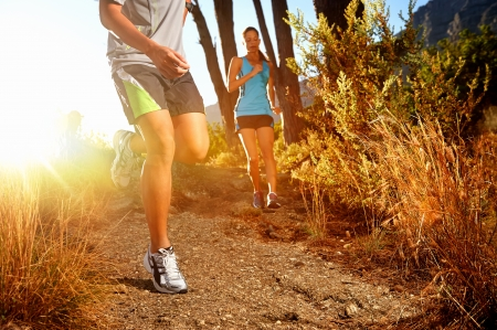 running man: Trail running marathon athlete outdoors sunrise couple training for fitness and healthy lifestyle