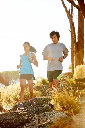 jog: Trail running marathon athlete outdoors sunrise couple training for fitness and healthy lifestyle