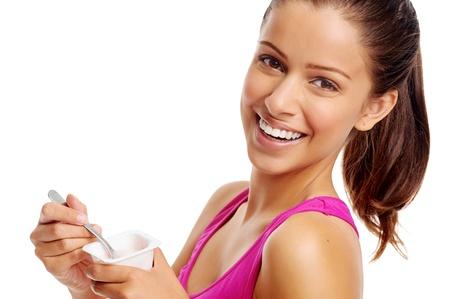 yogur: Mujer sana que come el yogur aislado en blanco