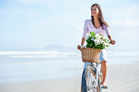 sea flowers: woman with bicycle and flowers in basket smiling carefree and happy