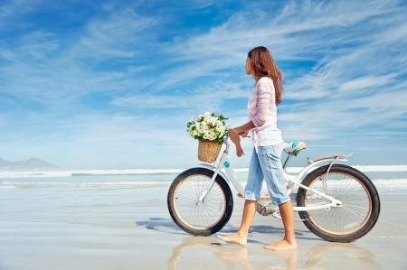 Vrouw met fiets bij het strand Stockfoto
