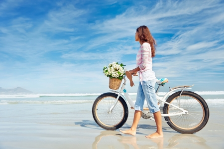 Woman with bike at the beach photo