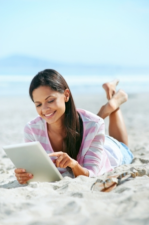 carefree woman uses touchpad tablet technology on the beach with internet vacation photo