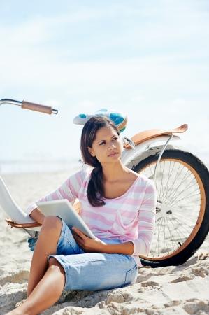 fiestas electronicas: Mujer con la tableta y la bicicleta en la playa