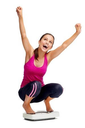 scale weight: happy healthy woman celebrates her weightloss on scale diet concept Stock Photo