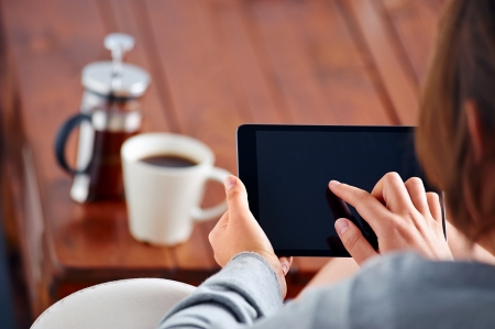 Young woman uses tablet while relaxing at home with coffee on the sofa couch photo