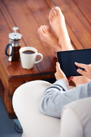 Young woman uses tablet while relaxing at home with coffee on the sofa couch Stock Photo - 19943899