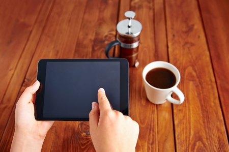 Young woman uses tablet while relaxing at home with coffee on the sofa couch Stock Photo - 19943913