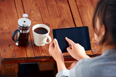 Young woman uses tablet while relaxing at home with coffee on the sofa couch Stock Photo - 20147523