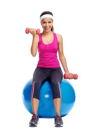 haciendo ejercicio: mujer haciendo ejercicio con pesas y el gimnasio bola suiza para la vida sana Foto de archivo