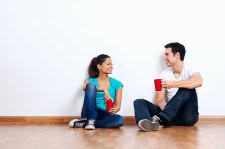 couple moving into empty new home sitting on floor together and drinking coffee Stock Photo - 20237000