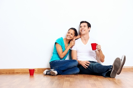 frau sitzt am boden: Paar bewegt sich in leere neue Heimat sitzen auf dem Boden zusammen und trinken Kaffee Lizenzfreie Bilder