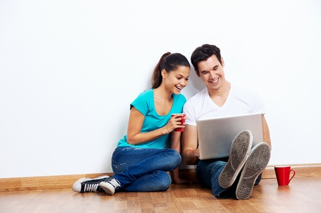 wireless laptop computer with couple sitting on floor in new empty apartment Stock Photo - 20237653