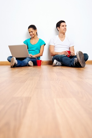 wireless laptop computer with couple sitting on floor in new empty apartment Stock Photo - 20236992
