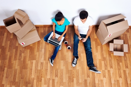 home moving: overhead view of couple sitting on floor together using computer wireless internet while moving into new home Stock Photo