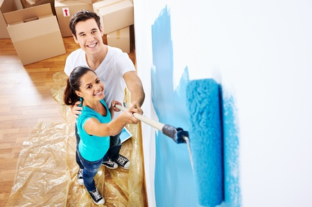 overhead view of couple having fun renovating their new home together with blue paint on a roller Stock Photo - 20237667