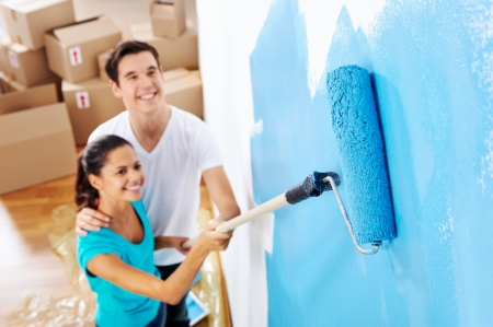 paintrush: overhead view of couple having fun renovating their new home together with blue paint on a roller