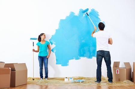 paint box: couple painting new home together with blue color happy and carefree relationship