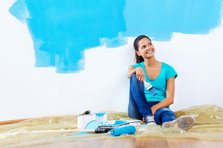 paintrush: confident young woman portrait while painting new apartment renovating with blue color paint