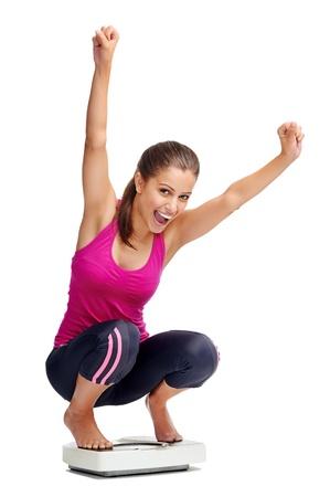 gelukkige gezonde vrouw viert haar gewichtsverlies op schaal dieet concept Stockfoto