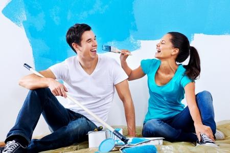 decorando: linda pareja pintura nueva casa junto retrato mientras estaba sentado en el piso de madera