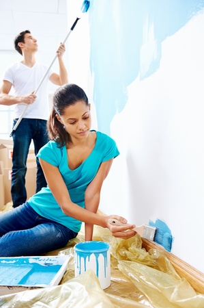 couple painting new home together with blue color happy and carefree relationship Stock Photo - 20237665