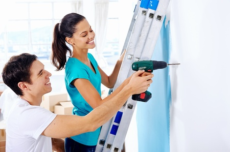 ladder safety: couple drilling in wall doing diy at new home after moving in together