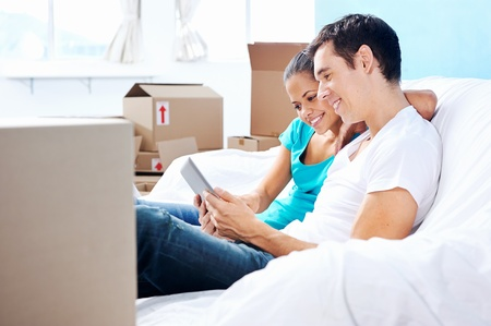 couple moving in together relaxing on sofa couch with laptop tablet computer and boxes