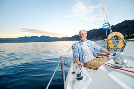 the retirement: carefree happy sailing man portrait of mature retired man on ocean boat at sunrise