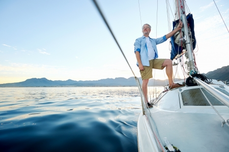 sailboat: sunrise sailing man on boat in ocean with flare and sunlight on calm morning on the water Stock Photo