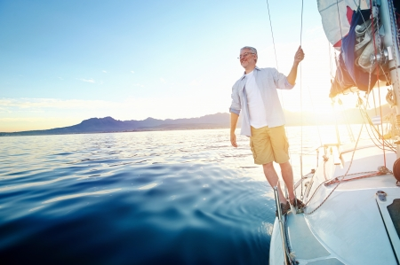 seniors: sunrise sailing man on boat in ocean with flare and sunlight on calm morning on the water Stock Photo