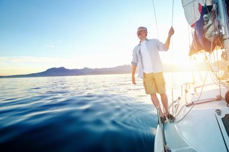 sunrise zeilen man op de boot in de oceaan met flare en zonlicht op kalme ochtend op het water