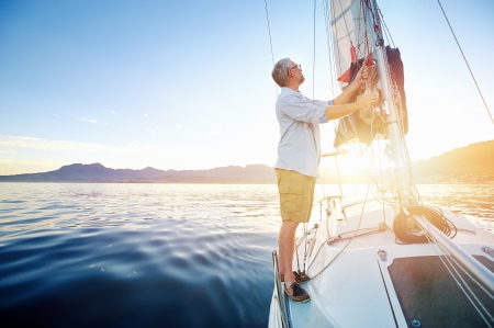 the yacht: sunrise sailing man on boat in ocean with flare and sunlight on calm morning on the water Stock Photo