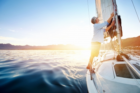 senior health: sunrise sailing man on boat in ocean with flare and sunlight on calm morning on the water Stock Photo