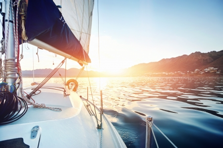 boat deck: Sailing yacht boat on on ocean water at sunrise with flare and outdoor lifestyle Stock Photo