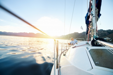 life is good: Sailing boat on on ocean water at sunrise with flare and outdoor lifestyle