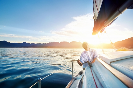 yachts: sunrise sailing man on boat in ocean with flare and sunlight on calm morning on the water Stock Photo