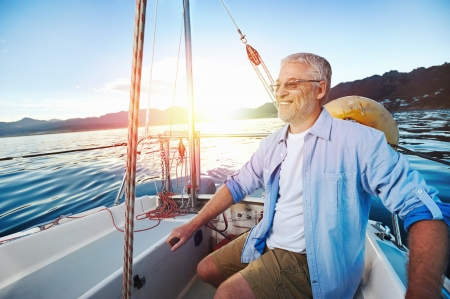 the retirement: successful retired man sailing portrait at sunrise on boat Stock Photo
