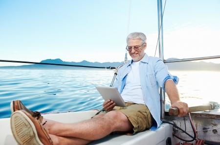 jubilados: hombre vela leyendo tablet PC en el barco con la tecnología moderna y el estilo de vida despreocupado retirado éxito superior