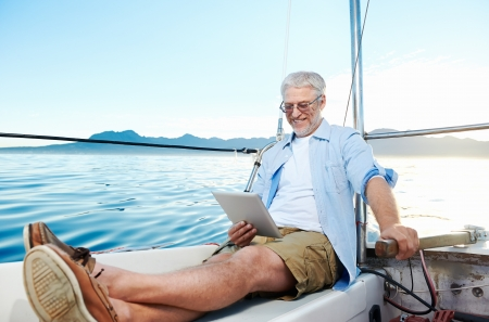 sailing man reading tablet computer on boat with modern technology and carefree retired senior successful lifestyle Stock Photo