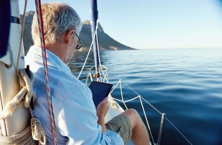 stile di vita: vela uomo che legge il computer tablet in barca con la tecnologia moderna e spensierato stile di vita anziano pensionato di successo